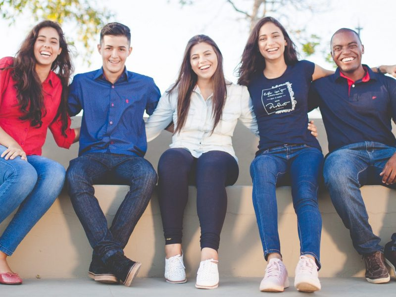 A young and diverse group smiling with arms around each other.