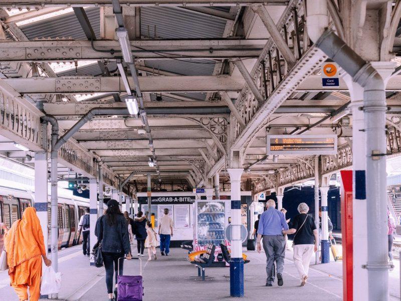 Individuals walking on a busy subway or train platform.